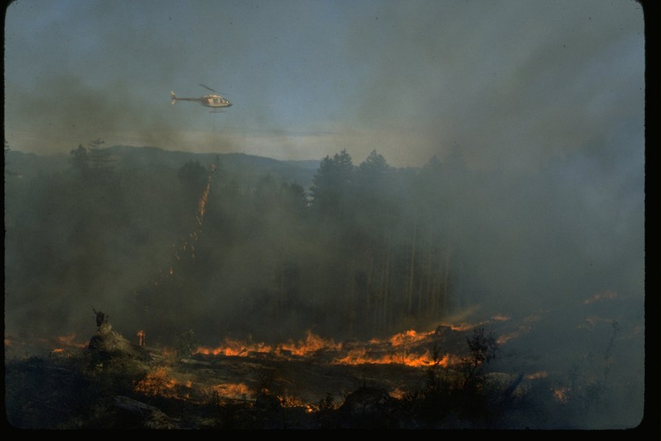 Helicopter flying over a forest fire.
