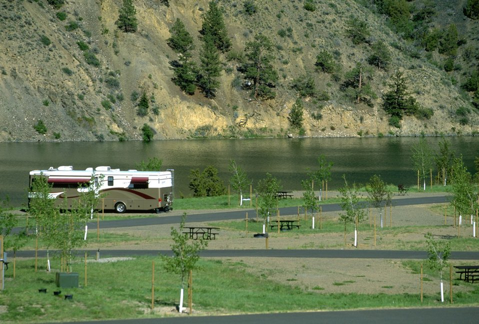 Newly- planted trees and recreational vehicle at Devils Elbow Campground
