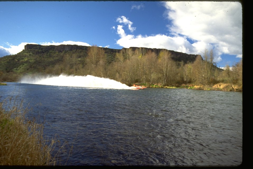 A jet boat is spraying up water in the Rogue River along the Lower Table Rock.