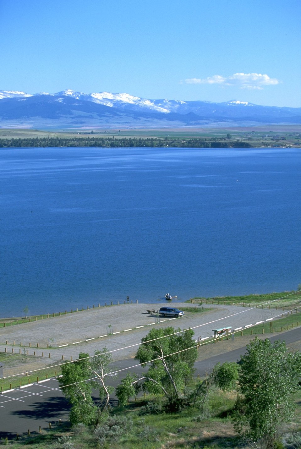 Scenic view of snow-capped mountains, Hauser Lake, and the parking lot of Clark's Bay Day Use Area