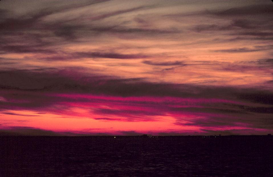Lurid colors mark a sunrise at sea off the eastern seaboard.