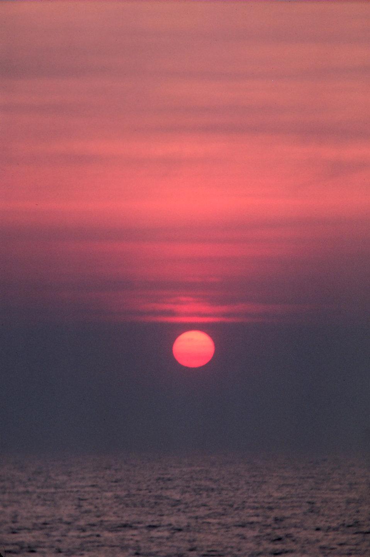 Sun as an orange sphere setting over the ocean.