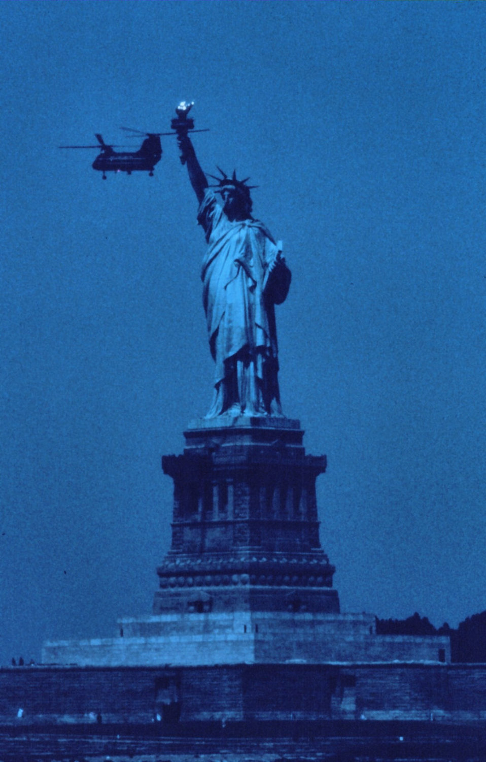 The Statue of Liberty, New York Harbor, with Navy helicopter during 1976 Bicentennial Tall Ship celebration