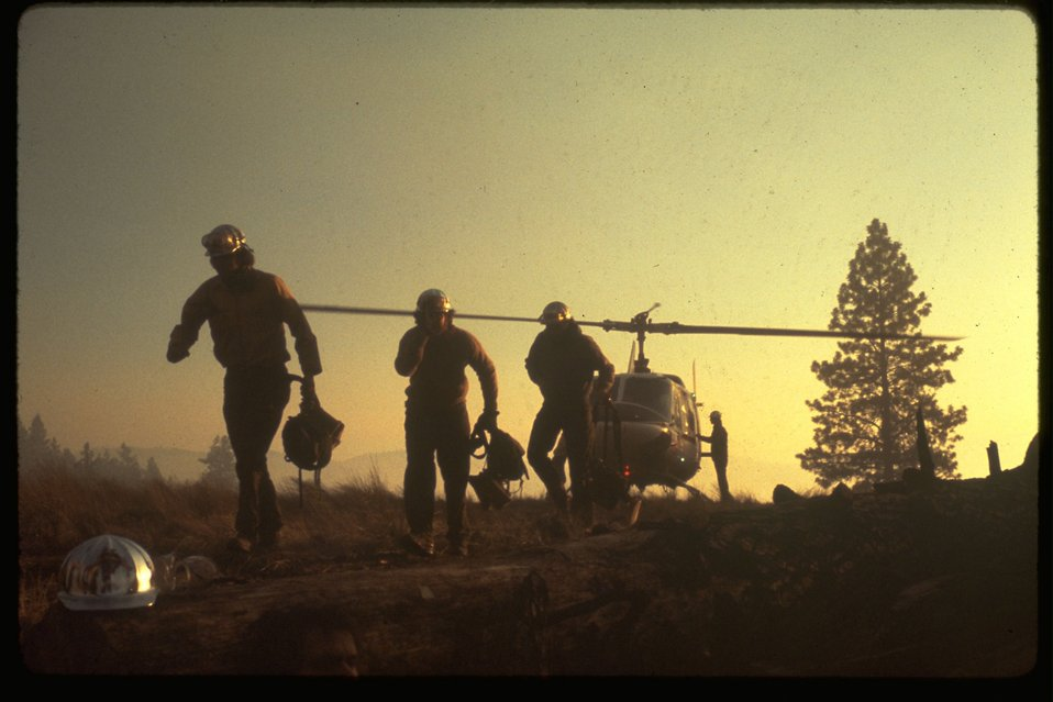 Firefighters unloading from a helicopter.