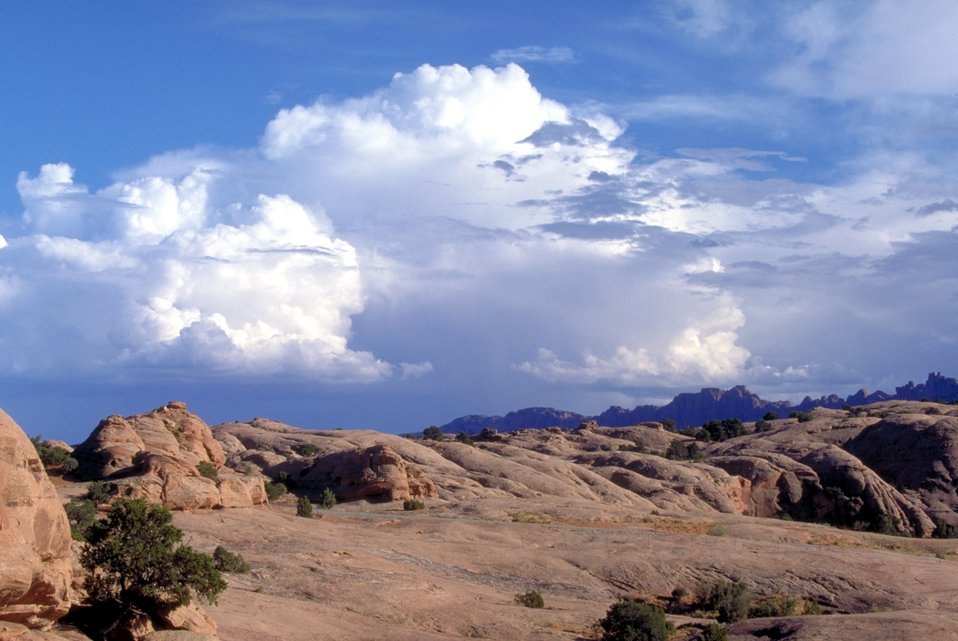 Slickrock and clouds with Behind The Rocks in the background near Moab, Utah.