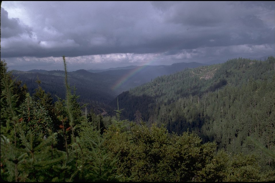Rogue River; farshot of rainbow in mountains.