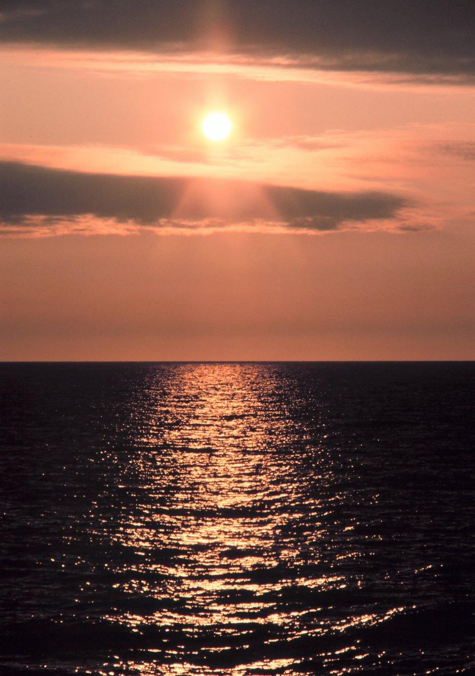 A streak of orange sunlight reflecting off the ocean at sunrise.