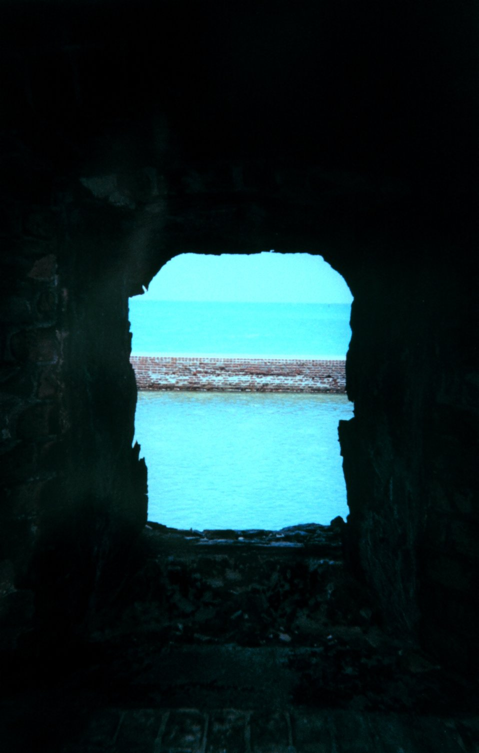 Looking through a cannon port towards the azure waters of the southern Gulf of Mexico.  These openings also served as air conditioning and let the sea breeze through.