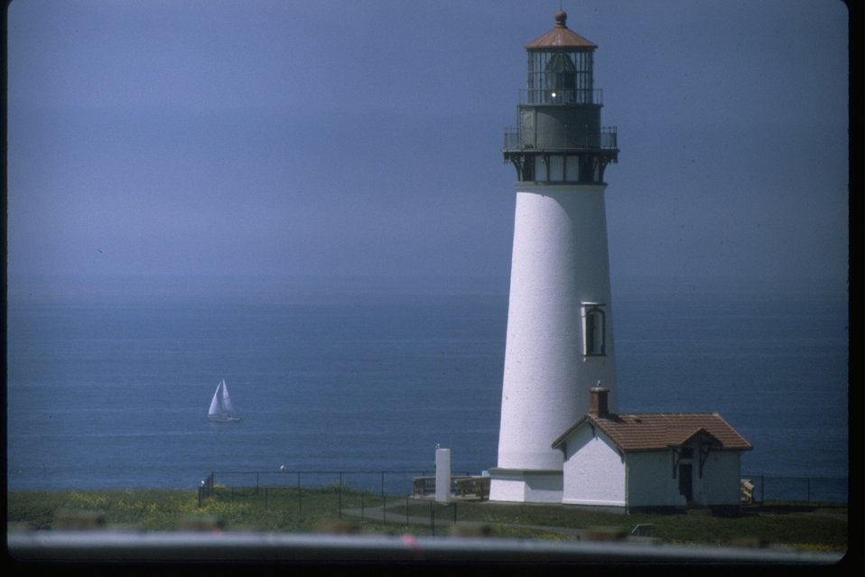 Horizontal shot of Yaquina Head lighthouse with a sailboat off shore.