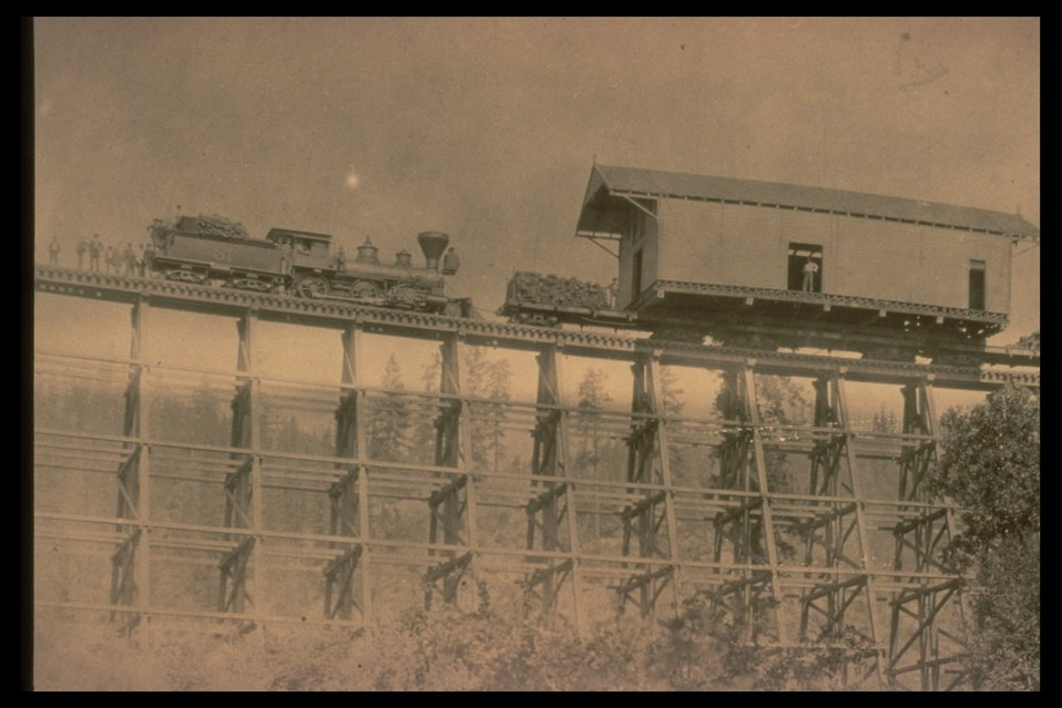 Black and White photo of a steam engine pushing a building on a flat car.