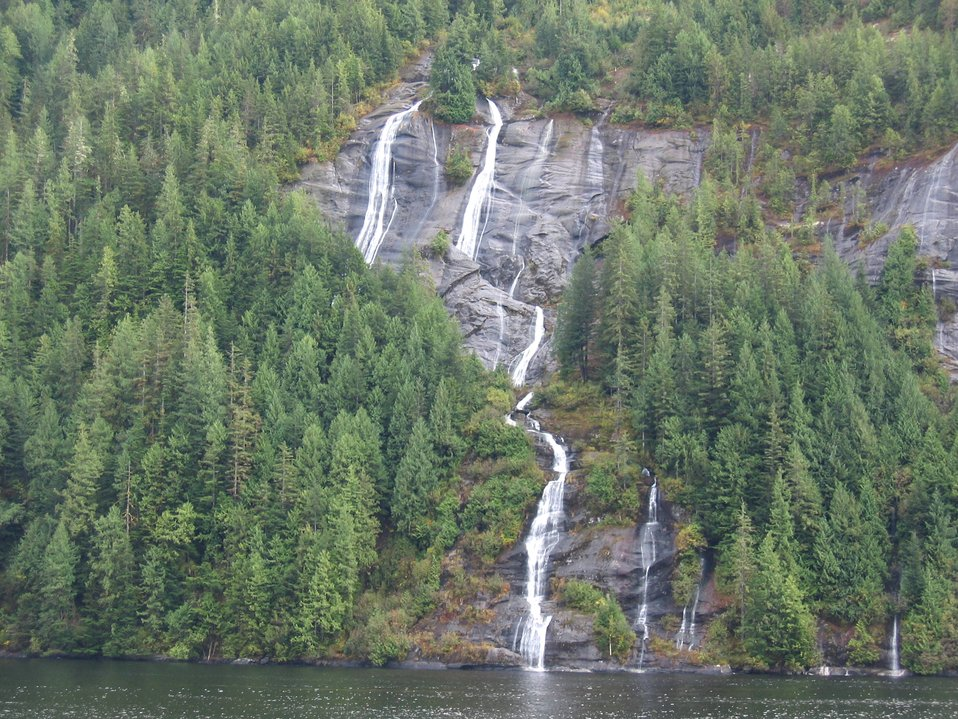 Dancing waterfalls, grey cliffs and evergreens at the edge of the sea.